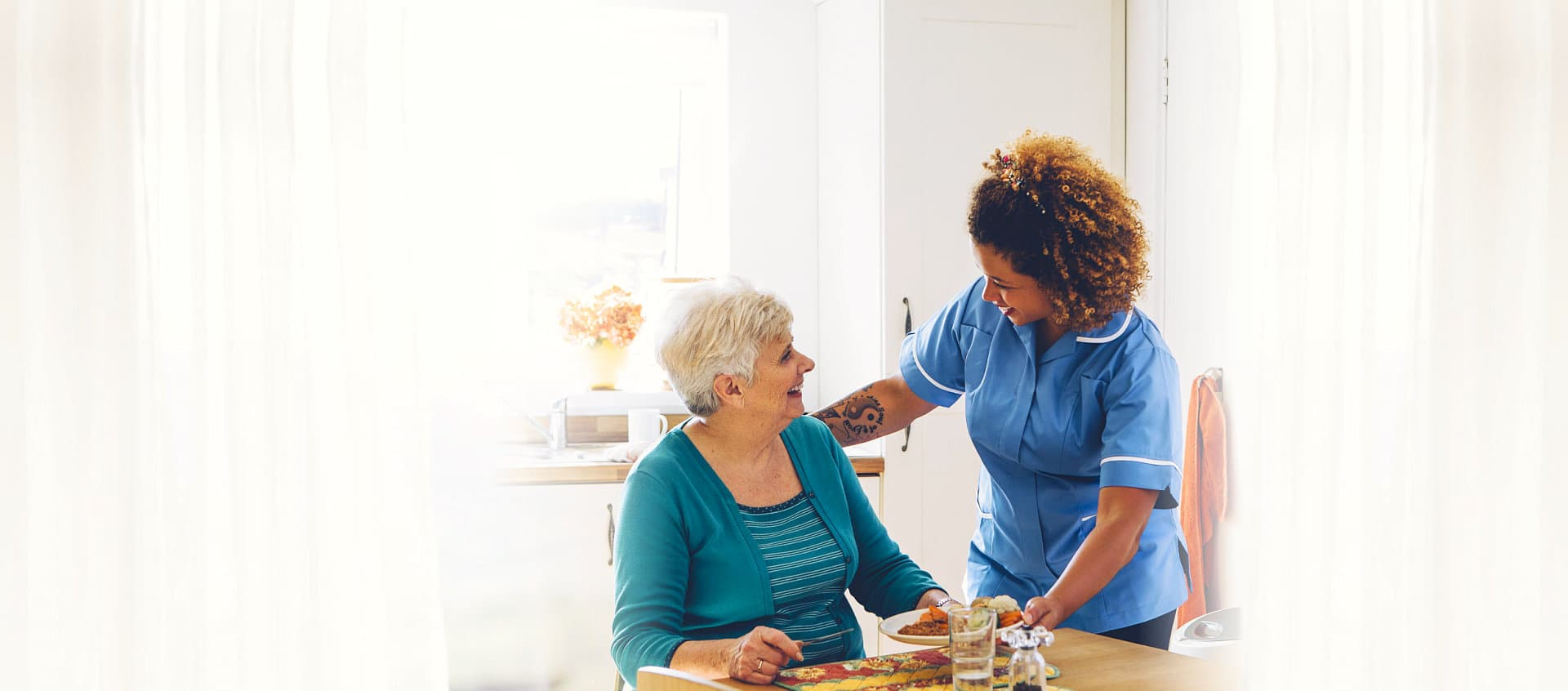 caregiver assisting patient in eating her meal