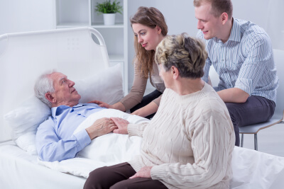 shot of an elderly man laying on a hospital bed and talking to his family
