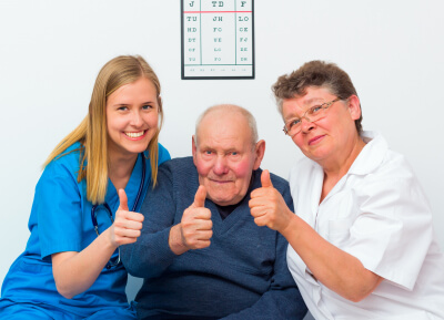 happy moments at the nursing home, elderly men showing thumbs up with his caregivers.