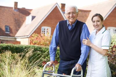 caregiver helps senior man to walk in garden using walking frame